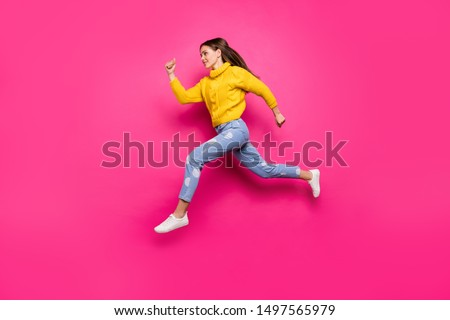 Full length profile side photo of concentrated youth jumping running fast looking ahead wearing yellow sweater dotted denim jeans isolated over fuchsia background