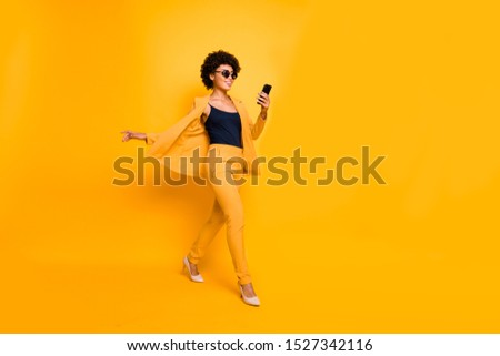 Full length profile side photo of positive afro american have spectacles weekend go use smartphone type sms on social network wear style outfit pants high-heels isolated yellow color background