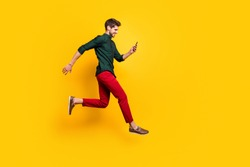 Full length profile side photo of positive cheerful guy use smartphone search discounts on social media jump run fast hurry wear green shirt red pants trousers isolated yellow color background