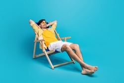 Full length profile side photo of positive guy traveler relax rest beach sun bathing lie comfort deckchair stretch hands wear white shorts isolated over blue color background