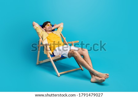 Full length profile side photo of positive guy traveler relax rest beach sun bathing lie comfort deckchair stretch hands wear white shorts isolated over blue color background Photo stock ©