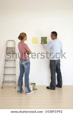 Full length rear view of a woman watch man testing paint colors on wall