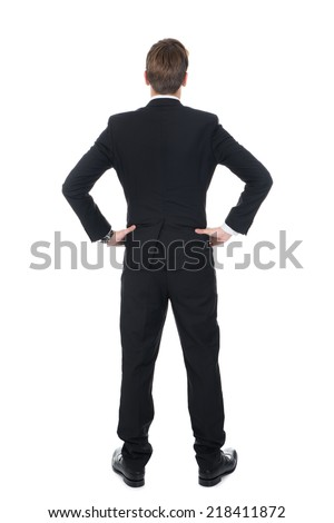 Full length rear view of confident businessman standing with hands on hips over white background #218411872