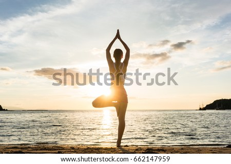 Full length rear view of the silhouette of a woman standing on one leg while practicing the tree yoga pose on a tranquil beach, shot at sunset during summer vacation in Indonesia