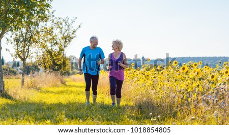 Full length rear view of two healthy senior people jogging on a country road against clear blue sky in summer