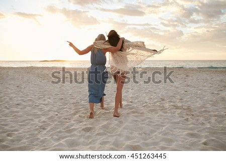 Shutterstock Full length rear view shot of two woman friends walking together on the beach. Female friends taking a walk on the sea shore and having fun.