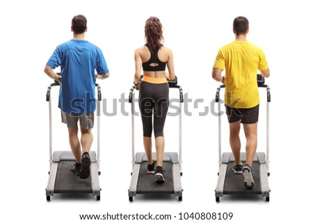 Full length rear view shot of two young men and a woman exercising on treadmills isolated on white background