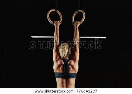 Full length rearview shot of a female athlete performing pull-ups on gymnastic rings. Fitness and crossfit woman with strong beautiful body exercising on gym rings health power endurance competitive #776641297
