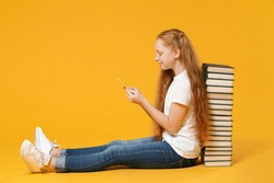 Full length redhead young girl 12-13 year old in white tshirt sit near big stack school book hold using mobile cell phone isolated on yellow background children studio portrait Kids education concept