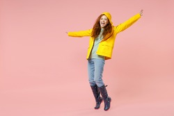 Full length redhead young woman in yellow waterproof raincoat outerwear stand on toes dancing leaning back isolated on pastel pink background studio Outdoors lifestyle wet fall weather season concept