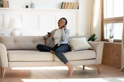 Full length relaxed young african american biracial woman resting on comfortable couch, dreaming listening favorite music in wireless headphones, choosing audio tracks in mobile app library at home.