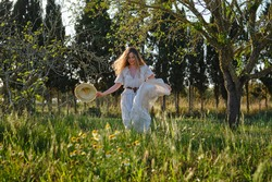 Full length sensitive content female wearing white maxi sundress strolling on verdant grassy meadow in lush summer park