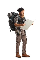 Full length shot of a bearded hiker with a backpack looking at a map isolated on white background