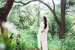 Full length shot of a beautiful young Indian woman in white dress walking in the forest