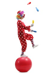 Full length shot of a clown juggling and standing on a ball isolated on white background