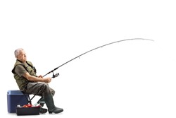 Full length shot of a fisherman on a chair with a fishing rod waiting for a catch isolated on white background