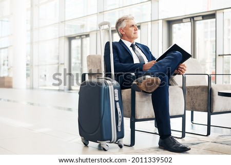 Full length shot of a handsome mature businessman looking contemplative while sitting in the office during the day Foto stock ©