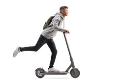 Full length shot of a male student with a backpack riding an electric scooter isolated on white background