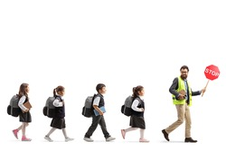 Full length shot of a male teacher in a safety vest walking with a stop sign and schoolchildren following behind isolated on white background