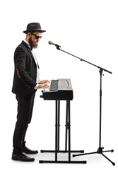 Full length shot of a man standing, playing a digital piano and singing on a microphone isolated on white background
