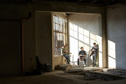 Full length shot of a rock band members playing music indoor.