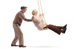 Full length shot of a senior man pushing a senior woman on a swing isolated on white background