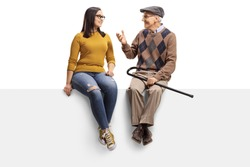 Full length shot of a senior man sitting on a panel and talking to a young girl isolated on white background