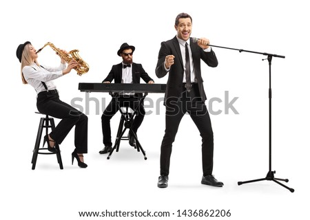 Full length shot of a woman playing sax, man playing a keyboard and a male singer singing on a microphone isolated on white background