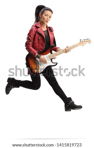 Full length shot of a young female guitarist playing a bass guitar and jumping isolated on white background