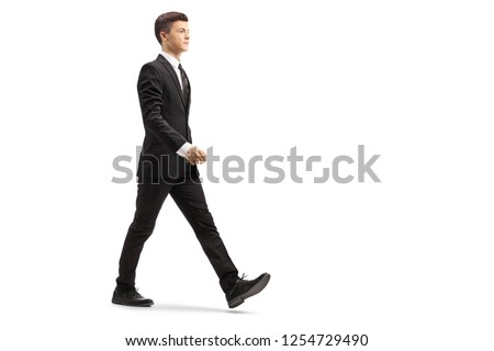Full length shot of a young handsome man in a black suit walking isolated on white background