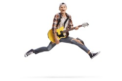 Full length shot of a young male musician playing an electric guitar and jumping isolated on white background