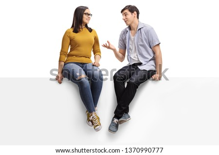 Full length shot of a young man sitting on a blank signboard and talking to a young woman isolated on white background