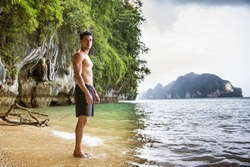 Full length shot of a young man standing on a beach in Phi Phi Island, Thailand, shirtless wearing boxer shorts, showing muscular fit body