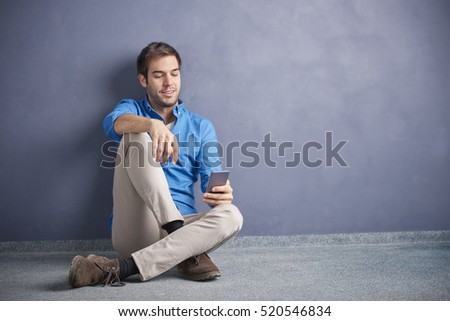 Full length shot of a young man using her cellphone while browsing on the social media. #520546834