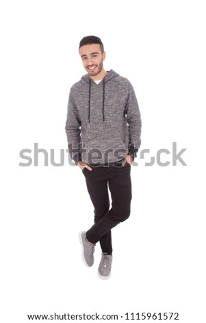 full-length shot of a young man wearing a casual outfit, standing crossed legs and putting his hands in his pocket, isolated on a white background. #1115961572