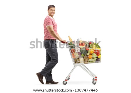 Full length shot of a young man with a shopping cart smiling at the camera isolated on white background