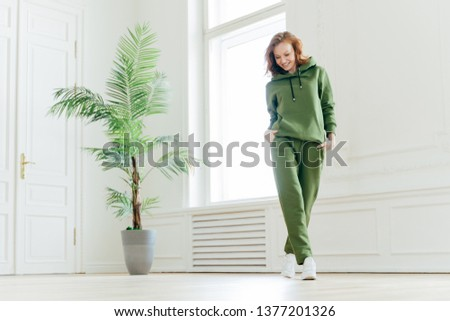 Full length shot of active pleased young woman with slim body, keeps hands in pockets of tracksuit, focused down, ready for doing cardio exercises, has determined look, pilates exercising indoor Stock photo ©