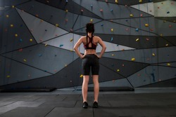 Full length shot of active young woman in sportswear going to climb, standing against artificial training climbing wall. Concept of sport life and rock climbing. Rear view. Focus on person