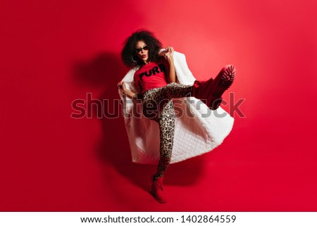 Full-length shot of adorable funny girl jumping on red background. Carefree african woman in long coat dancing in studio.