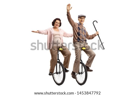 Full length shot of an elderly man holding a walking cane and an elderly woman riding unicycles and smiling isolated on white background #1453847792