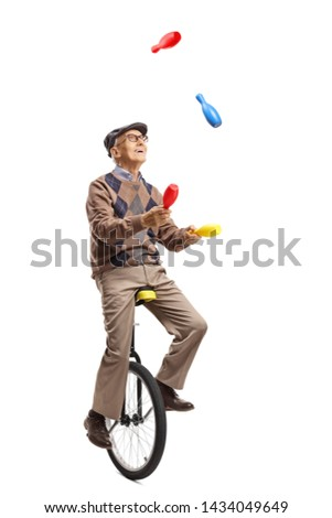 Full length shot of an elderly man juggling on a unicycle isolated on white background
