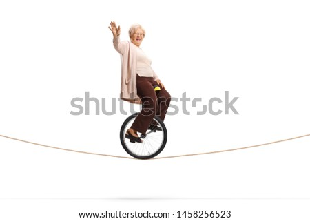 Full length shot of an elderly woman riding a unicycle on a rope and looking at the camera isolated on white background #1458256523