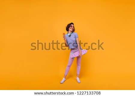 Full-length shot of attractive slim girl with longboard isolated on bright background. Romantic lady eating ice cream with pleasure during photoshoot.