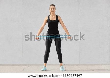 Full length shot of attractive sporty woman dressed in black sportsclothes, holds rubber resistance band, has workout at home, poses against grey background. People, endurance, determination #1180487497