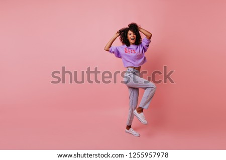 Full-length shot of attractive stylish woman dancing on rosy background. Appealing female model in jeans fooling around in studio.