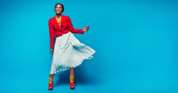 Full length shot of attractive woman in beautiful dress. African female fashion model standing over blue background with copy space.