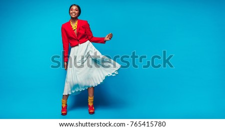 Full length shot of attractive woman in beautiful dress. African female fashion model standing over blue background with copy space. #765415780