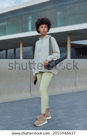 Full length shot of beautful African American woman dressed in sportsclothes carries rubber mat holds mobile phone going to have workout poses outside leads healthy lifestyle. People and sport Photo stock ©