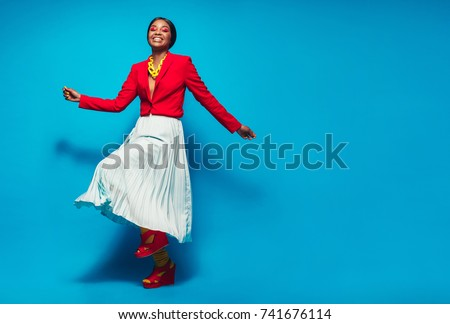 Full length shot of beautiful woman in stylish clothing standing over blue background. African female fashion model looking happy with copy space.