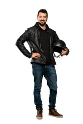 Full-length shot of Biker man posing with arms at hip and smiling over isolated white background